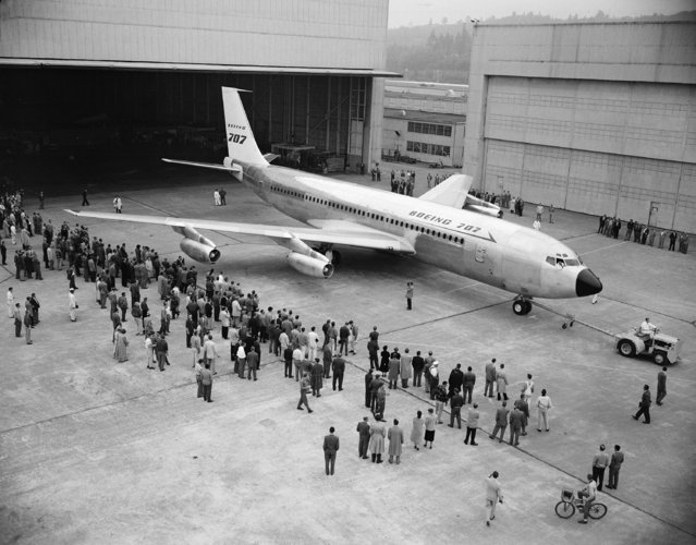 A small crowd of factory workers and officials watches as Boeing Airplane Company rolls America's first jet airliner at Renton, Wash., Monday, October 28, 1957.  The huge Boeing 707 Jet Stratoliner, capable of carrying 80 to 180 persons 5,000 miles nonstop at speeds of more than 600 miles an hour.  The jet will be delivered to Pan American World Airways. (Photo by AP Photo)