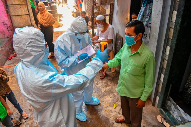 Medical staff wearing Personal Protective Equipment (PPE) gear conduct a door-to-door medical screening inside Dharavi slums to fight against the spread of the COVID-19 coronavirus, in Mumbai on June 24, 2020. The epidemic has badly hit India's densely populated major cities – including the national capital New Delhi and the financial hub Mumbai – with reports of hospitals being overwhelmed and patients struggling to find beds. (Photo by Indranil Mukherjee/AFP Photo)