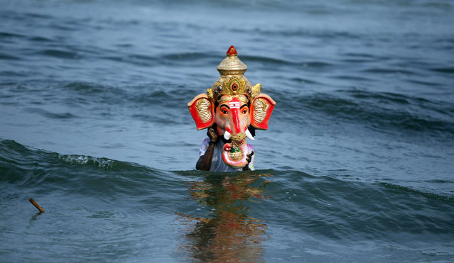 A man holds an idol of  Hindu God Ganesha before immersing it in the Bay of Bengal during Ganesh Chaturthi festival in Chennai, India, Sunday, September 20, 2015. The festival marks the birth of Ganesha who is widely worshiped by Hindus as the god of wisdom, prosperity and good fortune. (Photo by Arun Sankar K./AP Photo)