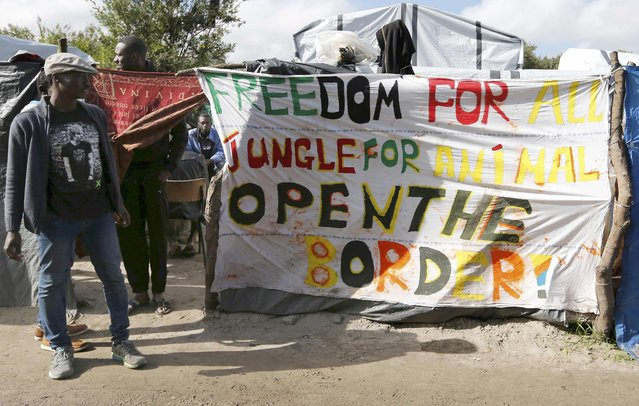 "Migrants stand near a banner which reads ""Freedom for all. Jungle for animal. Open the border"" at the makeshift camp called ""The New Jungle"" in Calais, France, September 19, 2015. (Photo by Regis Duvignau/Reuters)"