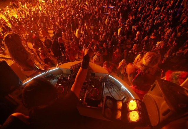 """People dance for a DJ at the Dancetronauts mutant vehicle during the Burning Man 2014 """"Caravansary"""" arts and music festival in the Black Rock Desert of Nevada, August 30, 2014. (Photo by Jim Urquhart/Reuters)"""