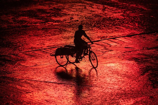 A trishaw driver crosses the road during a heavy rainfall in Yangon, Myanmar on June 29, 2020. (Photo by Shwe Paw Mya Tin/NurPhoto via Getty Images)