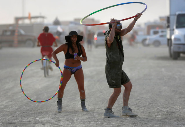 Participants hula-hoop as approximately 70,000 people from all over the world gather for the 30th annual Burning Man arts and music festival in the Black Rock Desert of Nevada, U.S. September 2, 2016. (Photo by Jim Urquhart/Reuters)