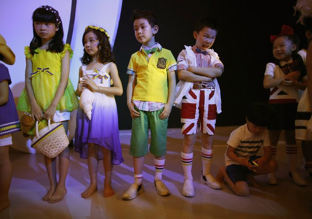 Child models wait for their turns at the backstage during a rehearsal for the Dong Wenmei T100 Children's Collection during China Fashion Week in Beijing October 29, 2014.    REUTERS/Kim Kyung-Hoon (CHINA - Tags: FASHION)