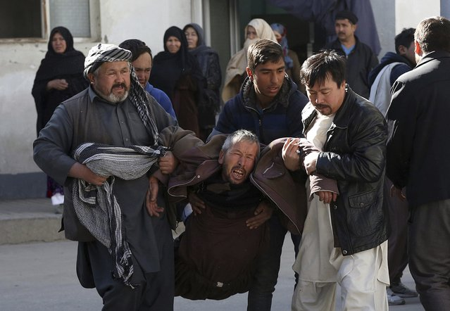 A distraught man is carried following a suicide attack in Kabul, Afghanistan, Thursday, December 28, 2017. Authorities say attackers stormed the Shiite Muslim cultural center in the Afghan capital Kabul, setting off multiple bombs and killing dozens. (Photo by Rahmat Gul/AP Photo)