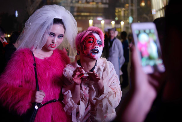 Revellers in costume pose for photos as they celebrate Halloween in Beijing on October 31, 2014. (Photo by Ed Jones/AFP Photo)