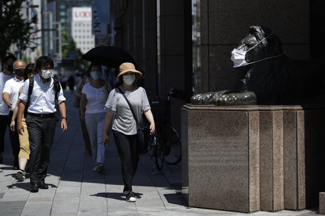 People wearing face masks to protect against the coronavirus walk by a statue of a lion decorated with a mask at a department store in Tokyo  Thursday, August 20, 2020. (Photo by Hiro Komae/AP Photo)