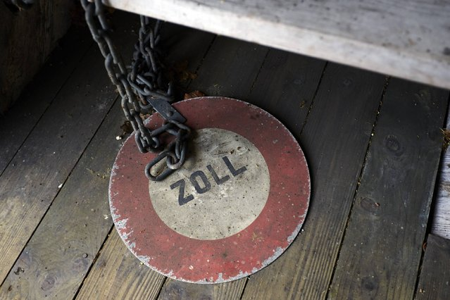 A Zoll (Customs) sign is seen on a wooden bridge over the Rhein river between Switzerland and Germany in Rheinau May 1, 2014. (Photo by Denis Balibouse/Reuters)