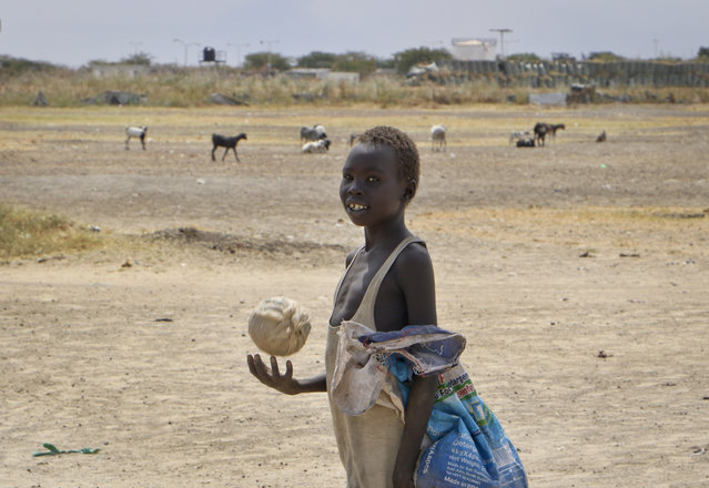 In this photo taken Sunday, December 9, 2018, a boy throws a ball while walking in the United Nations protection of civilians site in Bentiu, South Sudan. (Photo by Sam Mednick/AP Photo)
