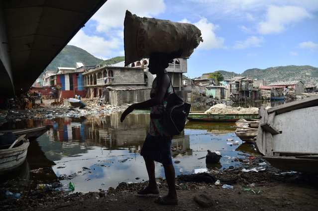 A woman walks next to the Mapou River, in Shadaa neighborhood, in Cap- Haitien, in the north of Haiti, 240 km from Port- au- Prince, ahead of Hurricane Irma on September 5, 2017. The monster hurricane coming on the heels of Harvey, which struck Texas and Louisiana late last month, is expected to hit a string of Caribbean islands including Guadeloupe late Tuesday before heading to Haiti and Florida. The Miami- based National Hurricane Center said Irma had strengthened to the most powerful Category Five, packing winds of 180 miles (280 kilometers) per hour. (Photo by Hector Retamal/AFP Photo)
