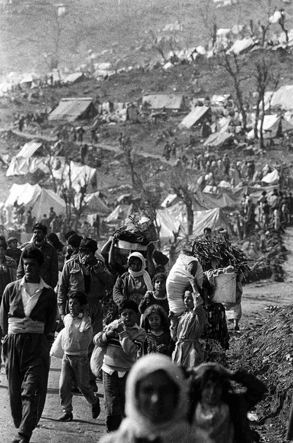"Iraqi Kurdish refugees carry their belongings in the Cukurca refugee camp in Turkey April 8, 1991. Reuters photographers have chronicled Kurdish refugee crises over the years. In 1991 Srdjan Zivulovic documented refugees in Cukurca who had escaped a military operation by Saddam Hussein's government in Iraq aimed at ""Arabising"" Kurdish areas in the north. (Photo by Srdjan Zivulovic/Reuters)"