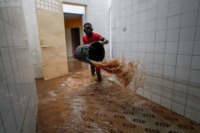A volunteer removes water from a flooded health center after heavy rains in Guediawaye on the outskirts of Dakar, Senegal on September 6, 2020. (Photo by Zohra Bensemra/Reuters)