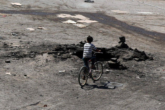 A boy rides a bicycle near a hole in the ground after an airstrike on Sunday in the rebel-held town of Dael, in Deraa Governorate, Syria September 19, 2016. (Photo by Alaa Al-Faqir/Reuters)
