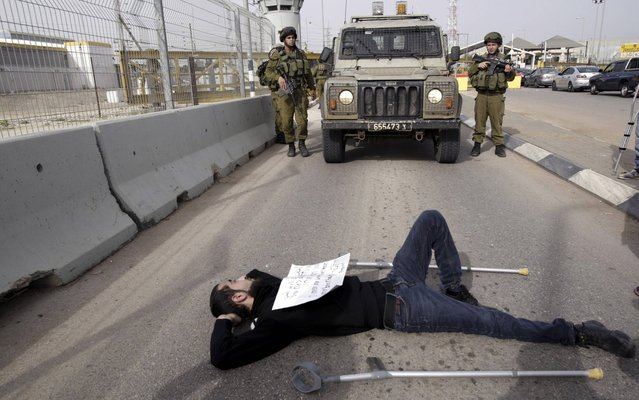 A Palestinian man lays in front of Israeli soldiers during a protest near an Israeli checkpoint in support of the Palestinian prisoners in Israeli jails north of the West Bank city of Jenin , Sunday, March 3, 2013. The fate of the prisoners is sensitive in Palestinian society, where virtually every family has had a member imprisoned by Israel. (Photo by Mohammed Ballas/AP Photo)