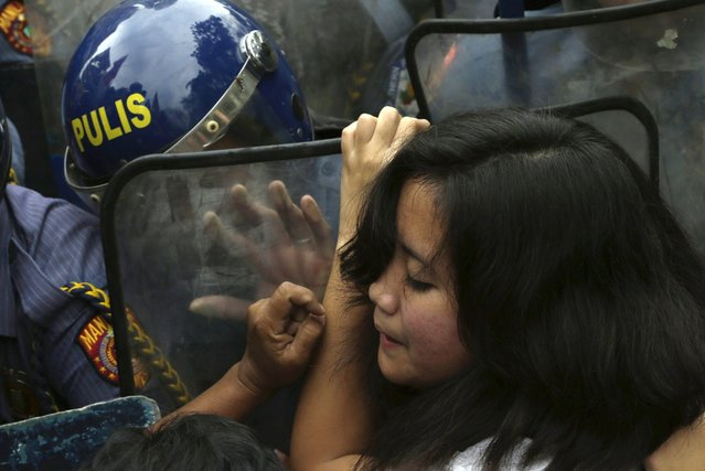 A Filipino protester tries to break through a row of riot police as her group is prevented from marching closer to the U.S. Embassy in Manila to commemorate International Women's Day in the Philippines, on March 8, 2013. Thousands of Filipinos commemorated Women's Day with calls to stop violence against women and children. (Photo by Bullit Marquez/AP Photo)