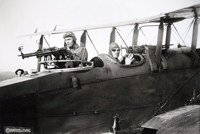 Two men at guns mounted in their airplane, photographed in 1920 by Harris & Ewing.