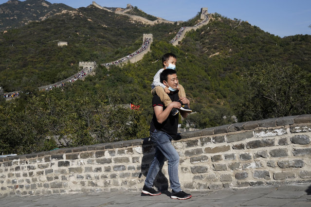 A man carries a child up a stretch of the Badaling Great Wall of China on the outskirts of Beijing on Tuesday, October 6, 2020. Chinese tourists took 425 million domestic trips in the first half of the eight-day National Day holiday, generating $45.9 billion in tourism revenue, according to China's ministry of culture and tourism. The holiday this year, which coincides with the Mid-Autumn Festival, will be a litmus test of whether China's tourism industry can bounce back after being battered by COVID-19. (Photo by Ng Han Guan/AP Photo)