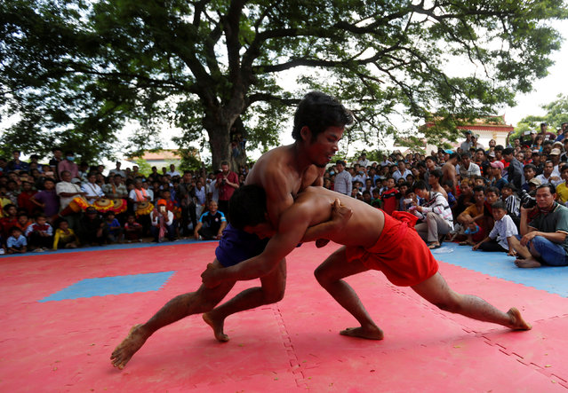 Men wrestle during the Pchum Ben festival, in Vihear Sour village in Kandal province, Cambodia, October 1, 2016. (Photo by Samrang Pring/Reuters)