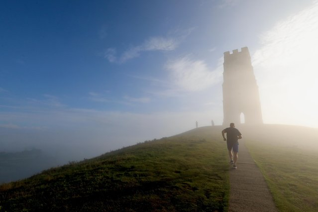 Glastonbury Tor in the English county of Somerset was shrouded in heavy fog on August 17, 2020, giving an early glimpse of autumn. (Photo by David Sims/Splash News and Pictures)