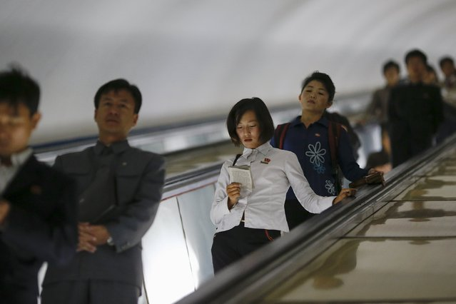 A woman reads a book as commuters make their way through a subway station in Pyongyang, North Korea October 9, 2015. (Photo by Damir Sagolj/Reuters)