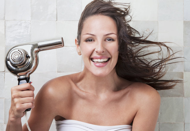 Young woman smiling, holding hairdryer with hair blowing. (Photo by Dimitri Otis/Getty Images)