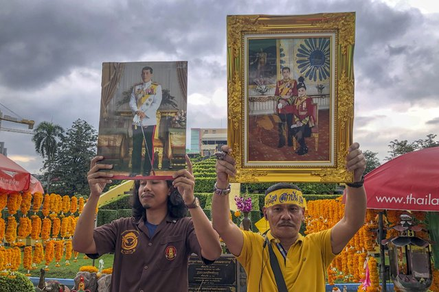 Supporters of monarchy display images of Thailand's King Maha Vajiralongkorn and Queen Suthida during a gathering to show their support at Ramkhamhaeng University in Bangkok, Thailand, Wednesday, October 21, 2020. A small group of royalist gathered to show their loyalty to the monarchy and declare they will defend the institution from any attacks. Royalists this week stepped up their activities online and in the streets, in counterpoint to ongoing student-led protests whose demands include reform of the monarchy to have it to better conform with democratic norms. (Photo by Peerayot Lakkananukul/AP Photo)