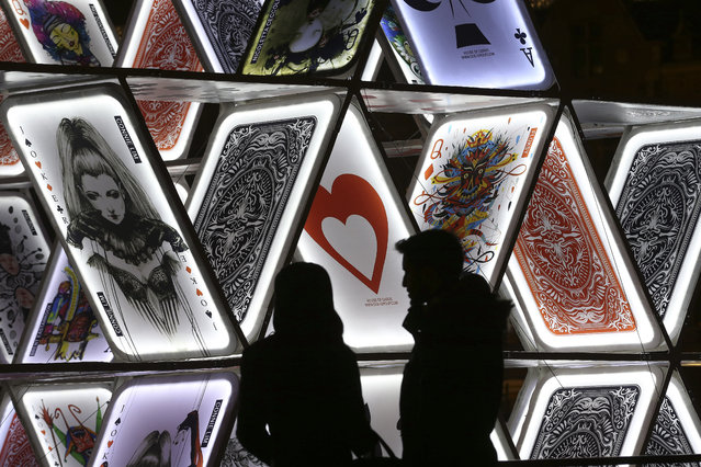 """In this Saturday, November 29, 2014 photo, a couple looks at a light sculpture called, """"House of Cards"""", by OGE Creative Group, from Israel, near Central Station in Amsterdam. The sculpture is a playful part of the Amsterdam Light Festival, which opened Nov. 27, 2014. (Photo by Peter Dejong/AP Photo)"""