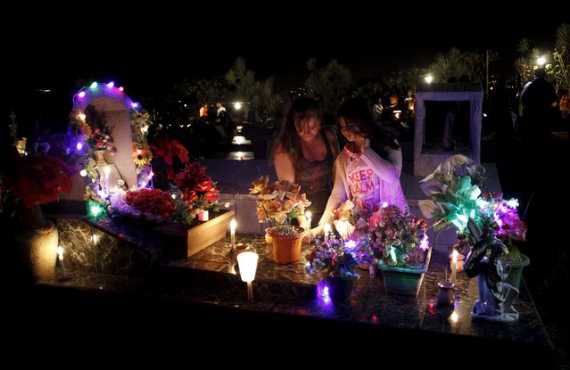 A mother and daughter take part in a vigil at the grave of a loved one at a cemetery in Barva de Heredia, Costa Rica, October 31, 2015. (Photo by Juan Carlos Ulate/Reuters)