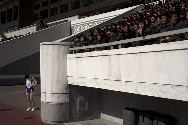 A marathon runner prepares herself as spectators watch at Kim Il Sung Stadium in Pyongyang, North Korea, Sunday, April 14, 2013. North Koreans held the 26th Mangyongdae Prize Marathon to mark the upcoming birthday of the late leader Kim Il Sung on April 15. (Photo by Alexander F. Yuan/AP Photo)