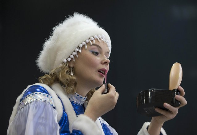 "A woman dressed as Snow Maiden prepares herself for the contest ""Yolka-fest-2014"" (Fir-festival-2014) in Minsk December 12, 2014. (Photo by Vasily Fedosenko/Reuters)"