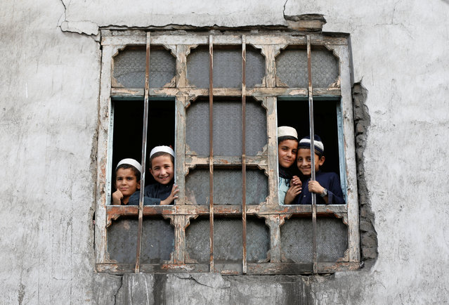 Afghan students from a religious school look on from a window of their school in Kabul, Afghanistan October 5, 2016. (Photo by Omar Sobhani/Reuters)