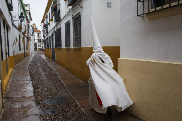 """A penitent leaves San Lorenzo Church after """"La Borriquita"""" procession was cancelled due to the rain during Palm Sunday on March 25, 2018 in Cordoba, Spain. Spain celebrates holy week before Easter with processions in most Spanish towns and villages. (Photo by Pablo Blazquez Dominguez/Getty Images)"""