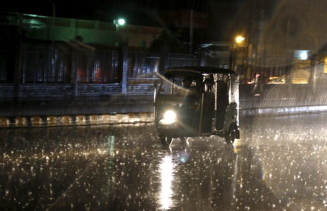 A rickshaw taxi drives in the rain on a road in Peshawar, Pakistan October 6, 2015. (Photo by Khuram Parvez/Reuters)