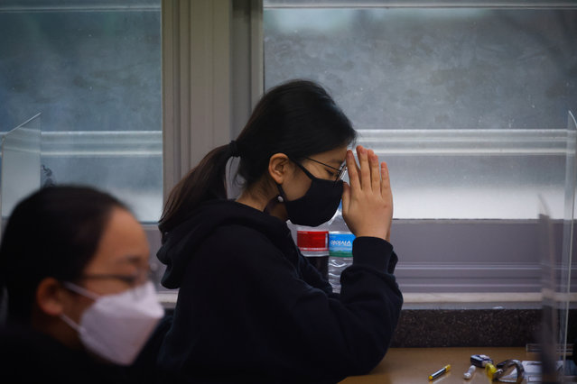 A student  wearing a face mask prays before the start of the annual college entrance examination amid the coronavirus pandemic at an exam hall in Seoul, South Korea, Thursday, December 3, 2020. South Korean officials are urging people to remain at home if possible and cancel gatherings as about half a million students prepare for a crucial national college exam. (Photo by Kim Hong-Ji/Pool Photo via AP Photo)