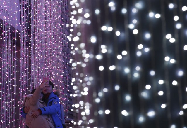 A couple takes a picture in front of a light installation for Christmas celebrations in Beijing December 23, 2014. (Photo by Kim Kyung-Hoon/Reuters)