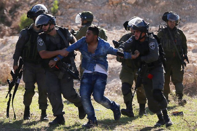 Israeli border police detain a Palestinian during clashes in the West Bank city of Tulkarm November 12, 2015. Israeli undercover forces raided a hospital in the West Bank on Thursday, shooting dead a Palestinian during an attempt to detain another man suspected of carrying out a stabbing, the Palestinian health ministry and doctors said. (Photo by Ahmad Talat/Reuters)