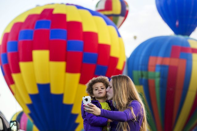 A woman and child take a photograph as hot air balloons lift off during the 2015 Albuquerque International Balloon Fiesta in Albuquerque, New Mexico, October 7, 2015. (Photo by Lucas Jackson/Reuters)