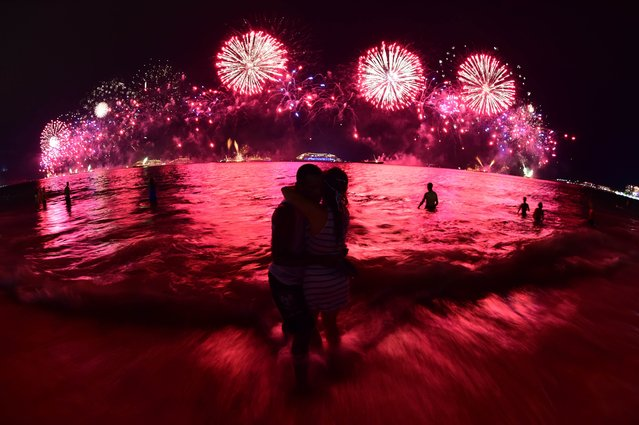 A couple (C) kisses during the fireworks for the new year on Copacabana beach in Rio de Janeiro on January 1, 2015. (Photo by Christophe Simon/AFP Photo)