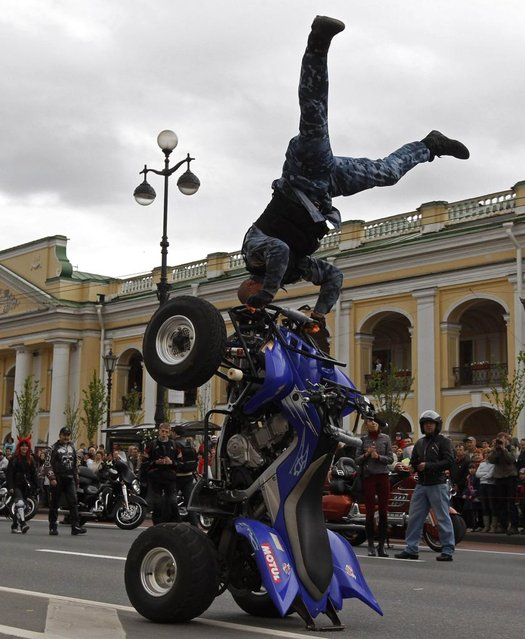 A biker demonstrates his skills on Nevsky Avenue in St. Petersburg, Russia, on May 26, 2013. Citizens of St. Petersburg on Sunday celebrated the 310th anniversary of the city's foundation by Russian Tsar Peter the Great. (Photo by Alexander Demianchuk/Reuters)