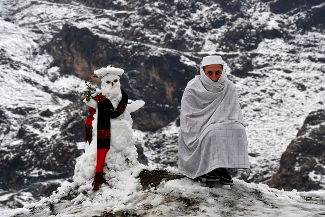 A man sits next to a snowman after first snowfalls in Landi Kotal on December 27, 2020. (Photo by Abdul Majeed/AFP Photo)