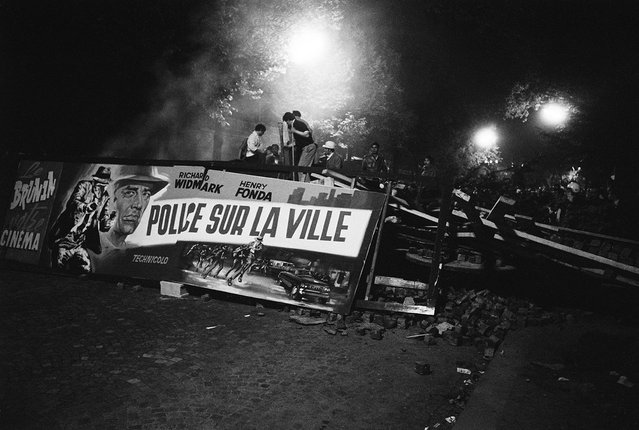 """Demonstrating students found a ready-made propaganda banner when they tore down a  movie marquee advertising a police film """"Police sur la Ville"""" (""""Madigan"""") co-starring Richard Widmark and Henry Fonda, Boulevard saint-Michel, Paris, France, May 10-11, 1968. (Photo by Gökşin Sipahioğlu/SIPA Press)"""