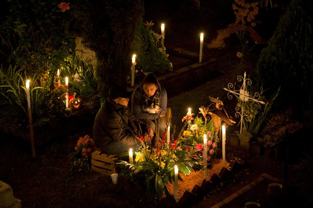 A couple sit beside a decorated child's grave during Day of the Dead at the San Gregorio cemetery in Mexico City, in the early morning hours of Tuesday, November 1, 2016. In a tradition that coincides with All Saints Day and All Souls Day on Nov. 1 and 2, families decorate the graves of departed relatives with marigolds and candles, and spend the night in the cemetery, eating and drinking as they keep company with their deceased loved ones. (Photo by Eduardo Verdugo/AP Photo)