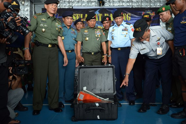 Tatang Kurniadi (R), head of the National Transportation Safety Committee, points at the flight data recorder of AirAsia QZ8501 as Indonesian Armed Forces Chief Moeldoko (C) looks on, onboard Indonesian navy vessel KRI Banda Aceh, in the Java Sea January 12, 2015. (Photo by Adek Berry/Reuters)