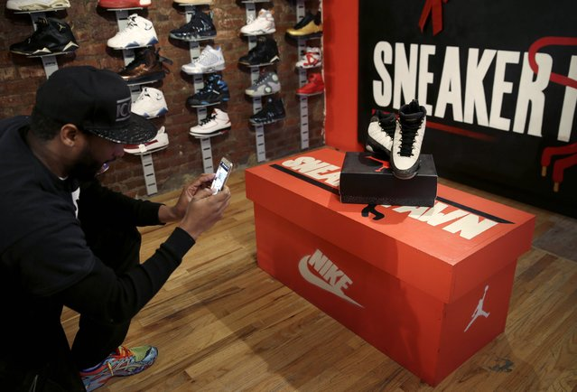 In this January 12, 2015 photo, Troy Reed takes a picture of a new inventory to post on social media at Sneaker Pawn in the Harlem section of New York, Monday, Jan. 12, 2015. Reed makes loans on high end athletic shoes used for collateral. (Photo by Seth Wenig/AP Photo)