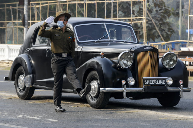 An Indian army soldier wearing a face mask to prevent the spread of the coronavirus marches alongside a vintage 1940 Austin A125 Sheerline car during rehearsals for Republic Day parade in Kolkata, India, Friday, January 22, 2021. (Photo by Bikas Das/AP Photo)