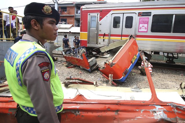 A police officer stands near the scene of an accident between a minibus and a commuter train at a railway crossing in West Jakarta December 6, 2015 in this photo taken by Antara Foto. (Photo by Rivan Awal Lingga/Reuters/Antara Foto)