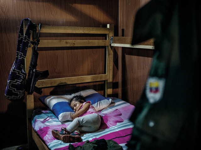 Sara Manuela, two, sleeps in a simple house of a Farc commander surrounded by a Farc uniform and a gun. Her mother and father both hold high positions inside the movement and have only decided to have a child because they believe in the peace process and the prospect of returning to civilian life. (Photo by Mads Nissen/Politiken/The Guardian/Panos Pictures)