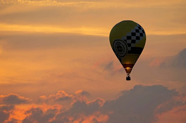 """A hot air balloon rises at the 19th annual international balloon festival """"Montgolfiade"""" in Heldelburg, Germany, on July 5, 2013. (Photo by Jens Meyer/Associated Press)"""