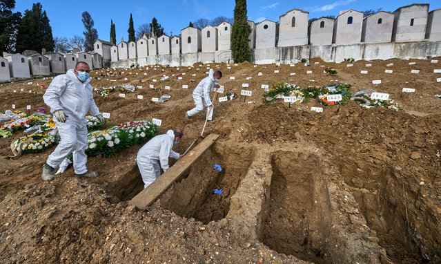 Gravediggers wearing protective gear prepare the grave of a COVID-19 victim at Cemitério do Alto de São João (Alto de São João Cemetery) during the COVID-19 Coronavirus pandemic on February 25, 2021 in Lisbon, Portugal. Alto de São João Cemetery, one of the country's largest, has been dealing with a large number of COVID related burials and cremations. (Photo by Horacio Villalobos/Corbis via Getty Images)