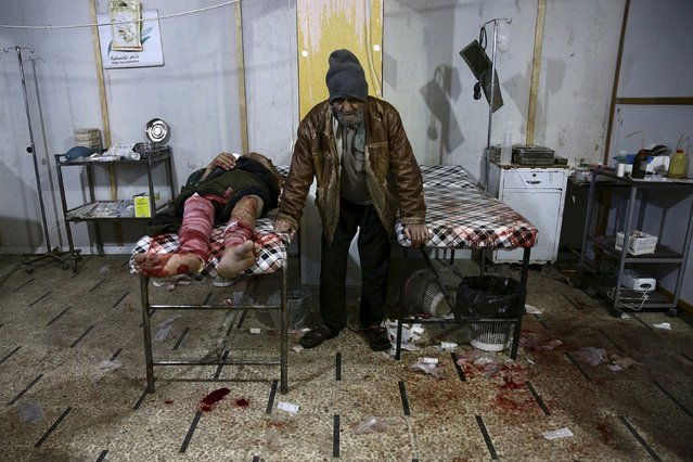 A man, injured in what activists said was an airstrike by forces loyal to Syria's president Bashar al-Assad, rests inside a field hospital in the Douma neighborhood of Damascus, Syria December 6, 2015. (Photo by Bassam Khabieh/Reuters)